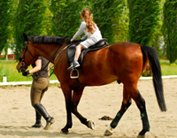רכיבה טיפולית - ילדה רוכבת על סוס עם מדריכת רכיבה